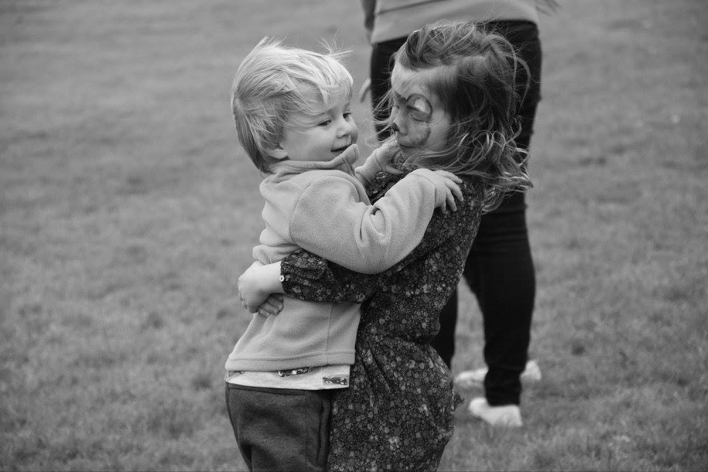 Two children playing, a girl giving a boy a hug